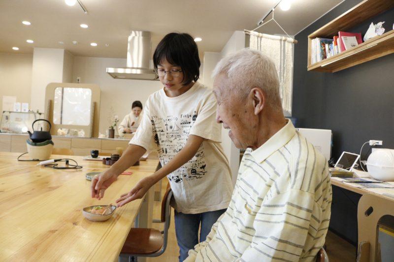 女の子がおじいちゃんにお茶を出している画像